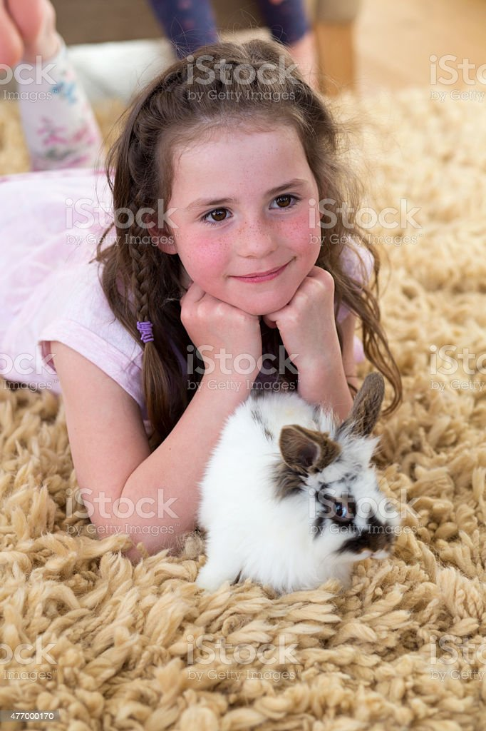 A brunette little girl at home with her pet rabbit. The rabbit is...