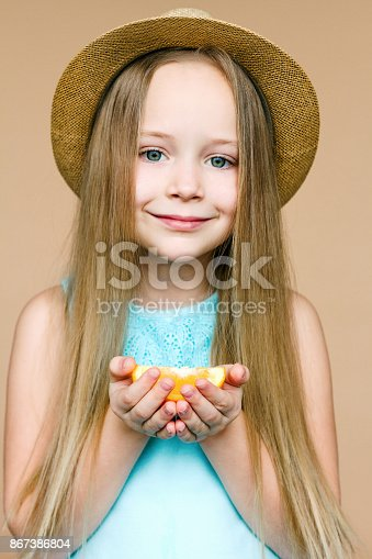 istock Little girl with piece of orange 867386804