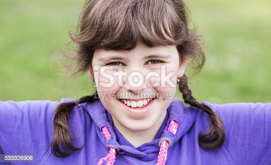 149051793 istock photo Little girl with pigtails happily spends time outdoors. 533326906
