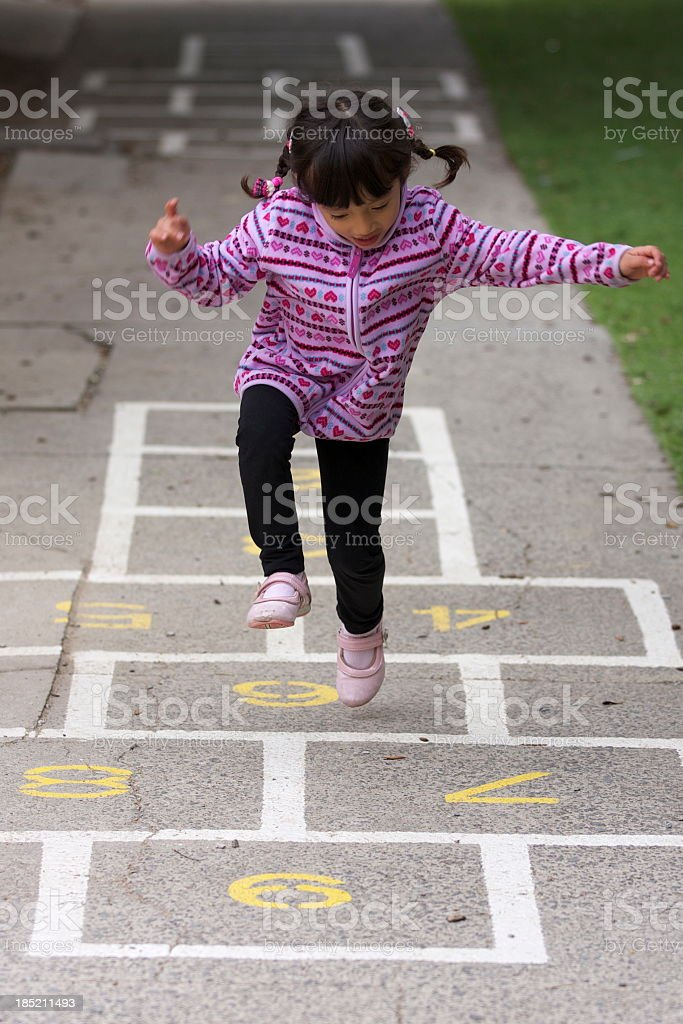 Little girl with pigtails playing hopscotch stock photo