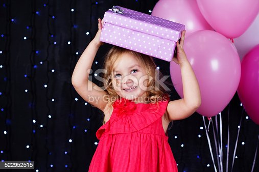 istock Little girl with pink balloons and gift boxes 522952515