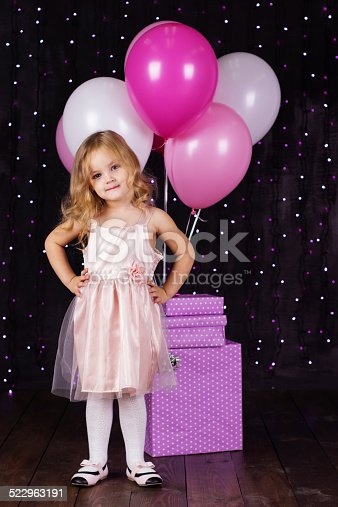 istock Little girl with pink balloons and gift boxes 522963191