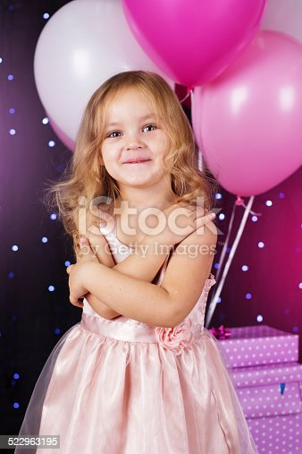 istock Little girl with pink balloons and gift boxes 522963195