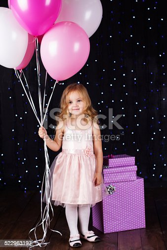 istock Little girl with pink balloons and gift boxes 522963197