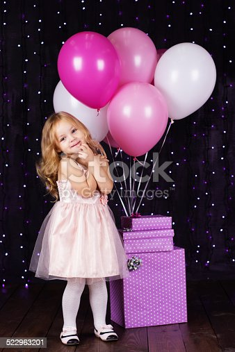 istock Little girl with pink balloons and gift boxes 522963201