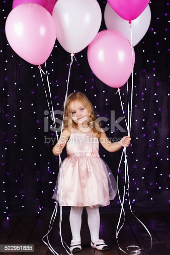 istock Little girl with pink balloons 522951835