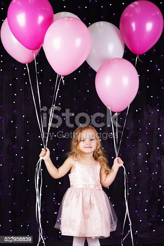 istock Little girl with pink balloons 522958839