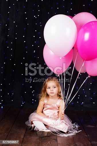 istock Little girl with pink balloons 522959657