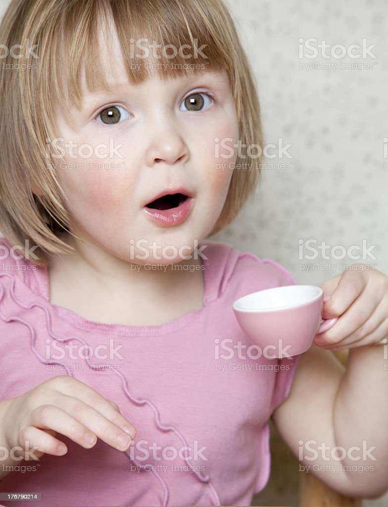 Little girl with pink cup playing a tea party royalty-free stock photo