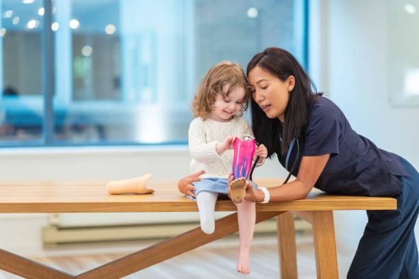 liten flicka med protetiska ben vid läkarbesök - protesutrustning bildbanksfoton och bilder