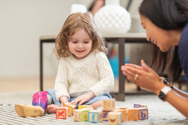 Little girl with prosthetic leg at occupational therapy appointment stock photo