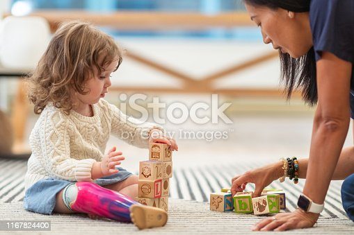 A preschool age girl with a prosthetic leg is at a medical appointment. The child is meeting with her physical therapist. The child is sitting on the floor building with wooden toy blocks. The medical professional is sitting on the floor assisting the girl.