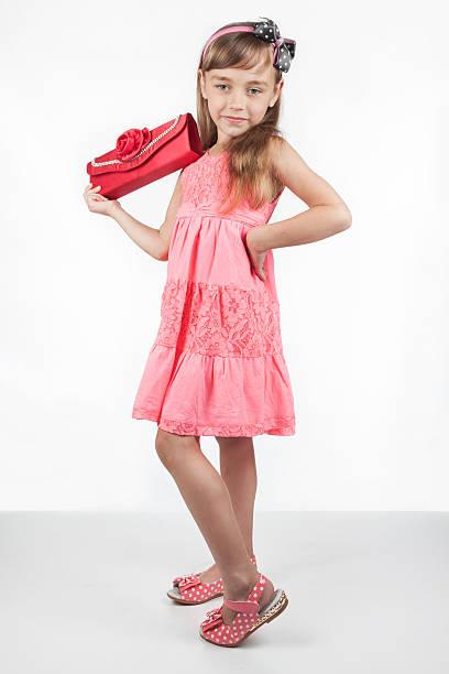 kleines mädchen mit roten tasche für einen erwachsenen - kinderhandtaschen stock-fotos und bilder