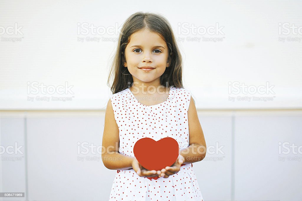 Little girl with red heart stock photo