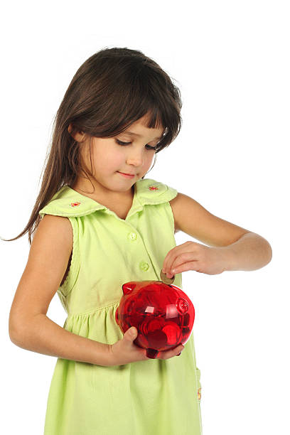 Little girl with red piggy bank  append stock pictures, royalty-free photos & images