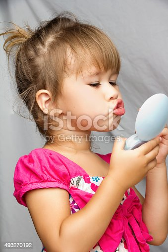 511527698 istock photo Little girl with small mirror, playing adult 493270192