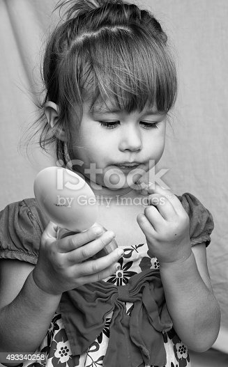 istock Little girl with small mirror, playing adult 493340258