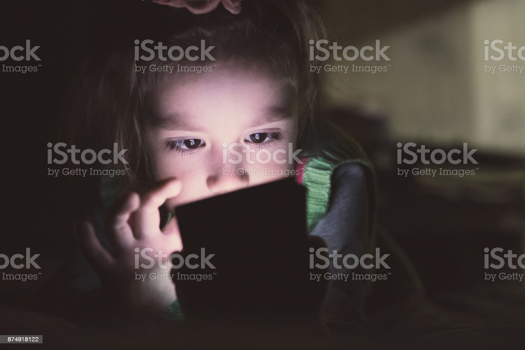 Little girl with smartphone lying in a bed, stock photo