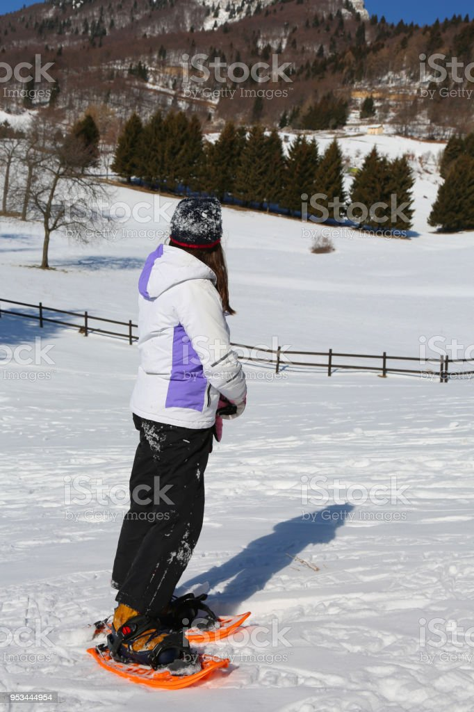 little girl with snowshoes stops to look at the horizon stock photo