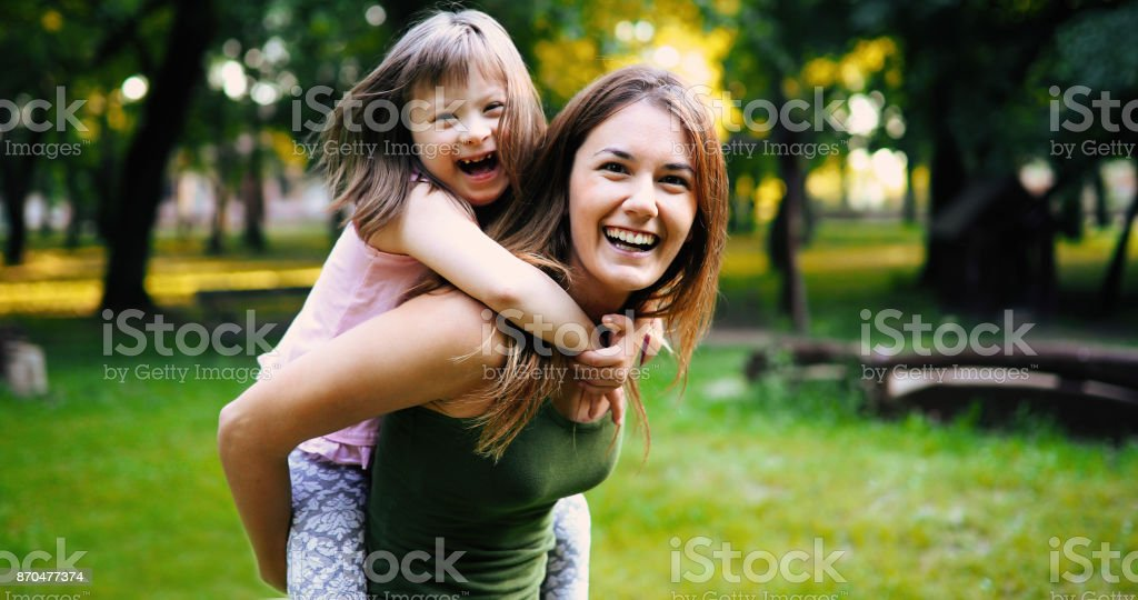 Little girl with special needs enjoy spending time with mother stock photo