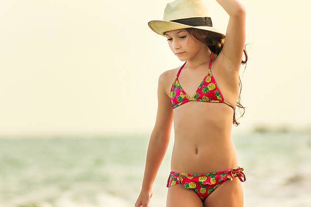 Little Girl with Straw Hat Walking at the Beach stock photo