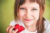 Smiling little girl holding a bitten strawberry
