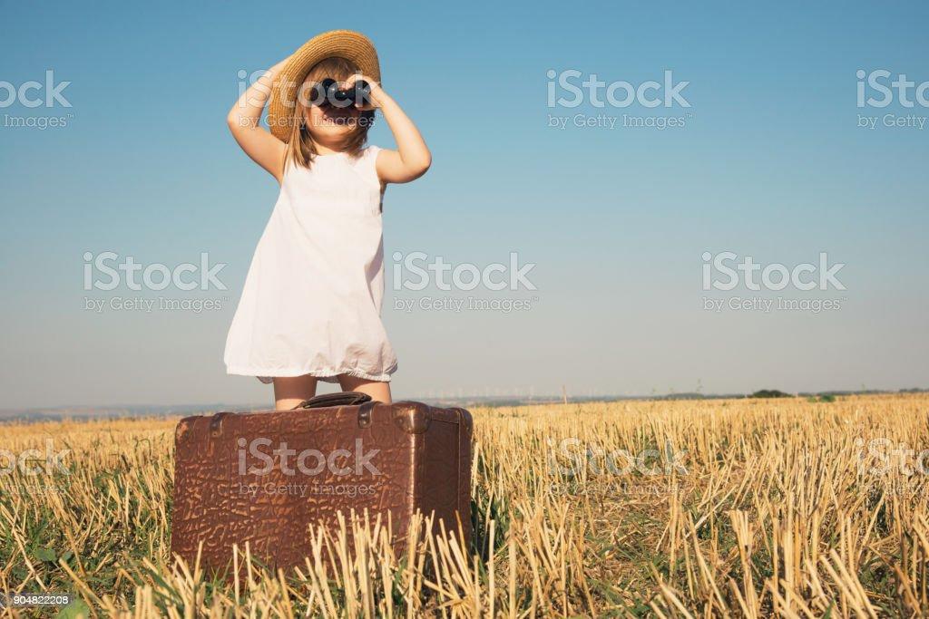 Kleines Mädchen mit Koffer sucht Trog Fernglas – Foto
