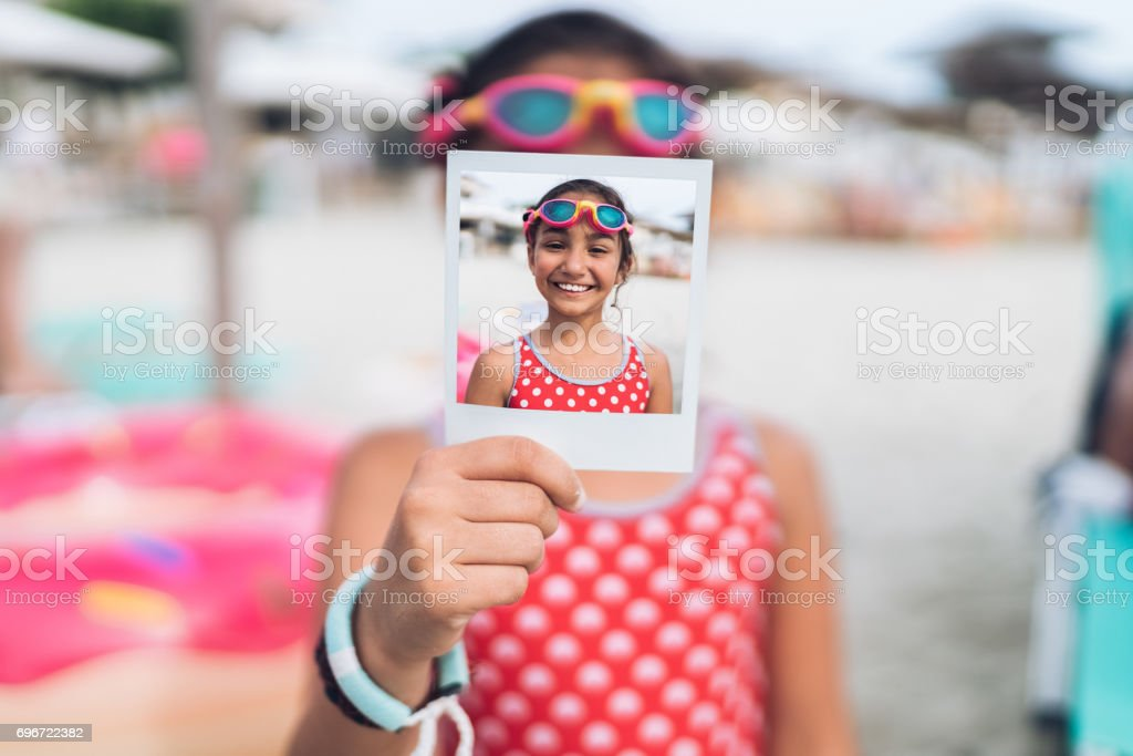Little girl with swimming googles showing instant photo stock photo