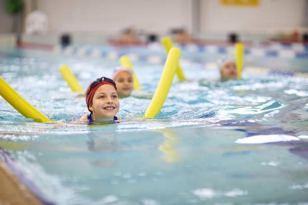 niña con tallarines que nadan - natación fotografías e imágenes de stock