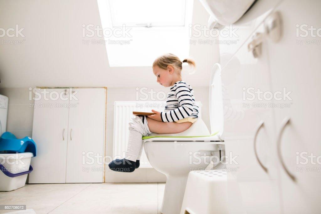 Kleines Mädchen mit Tablet auf der Toilette sitzend. – Foto
