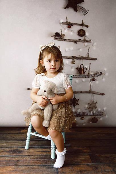 kleines mädchen mit teddy-bär von weihnachtsbaum - glitter farbige wände stock-fotos und bilder
