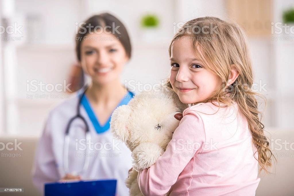 Little girl with teddy bear goes to doctor's stock photo