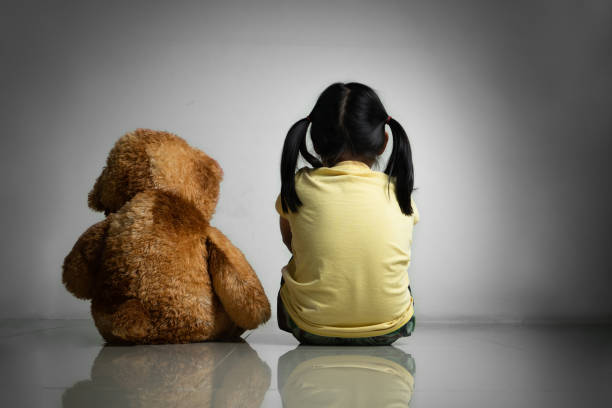 Little girl with teddy bear sitting on floor at empty room. Mental and depressed family concept. Back view stock photo
