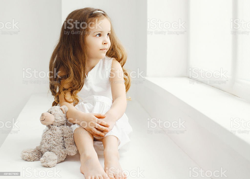 Little girl with teddy bear toy home in room sitting stock photo