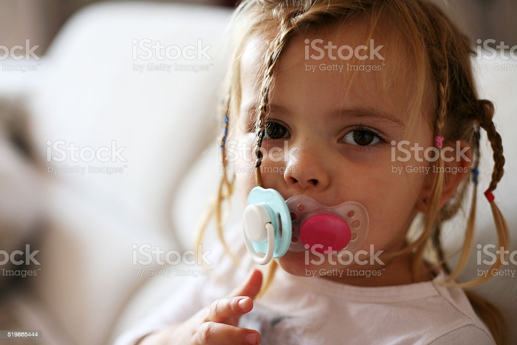 Little girl with two pacifiers. stock photo