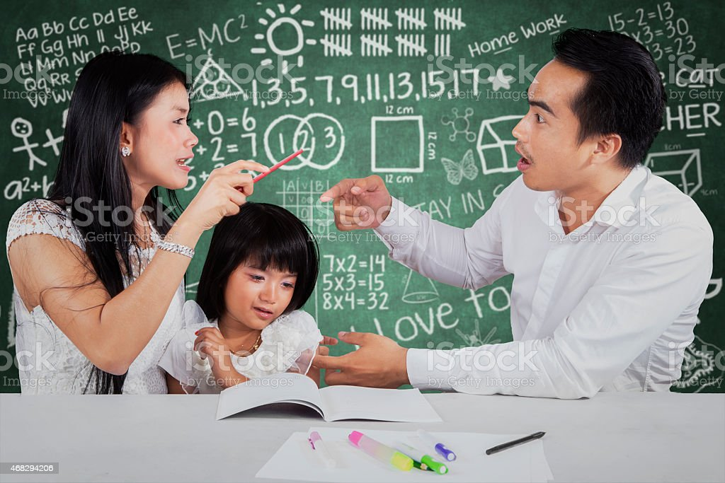 Little girl with two parents quarreling stock photo