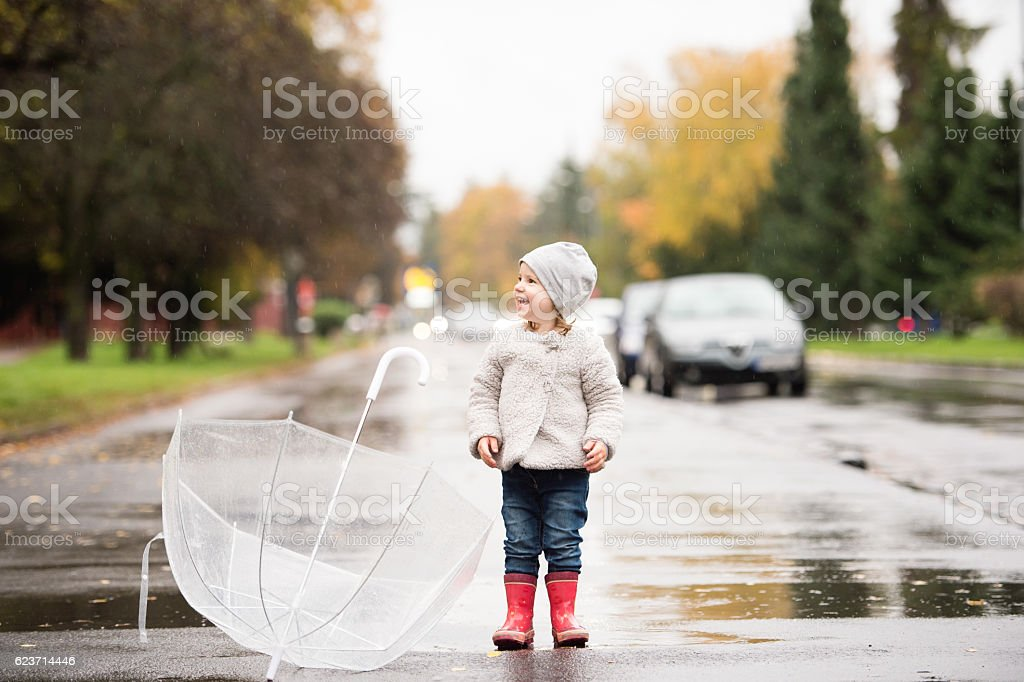 Little girl with umbrella jumping in a puddle, rainy day. stock photo