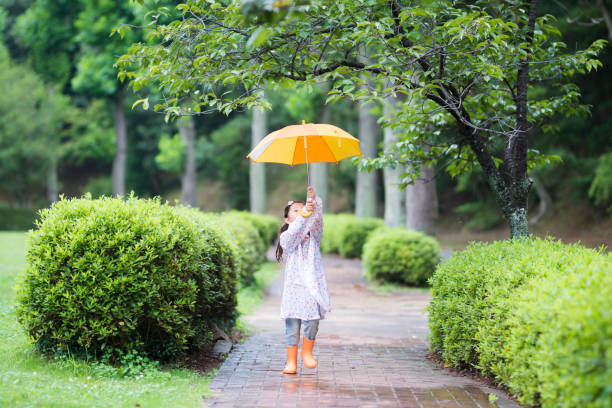 kleines mädchen mit regenschirm - regenzeit stock-fotos und bilder