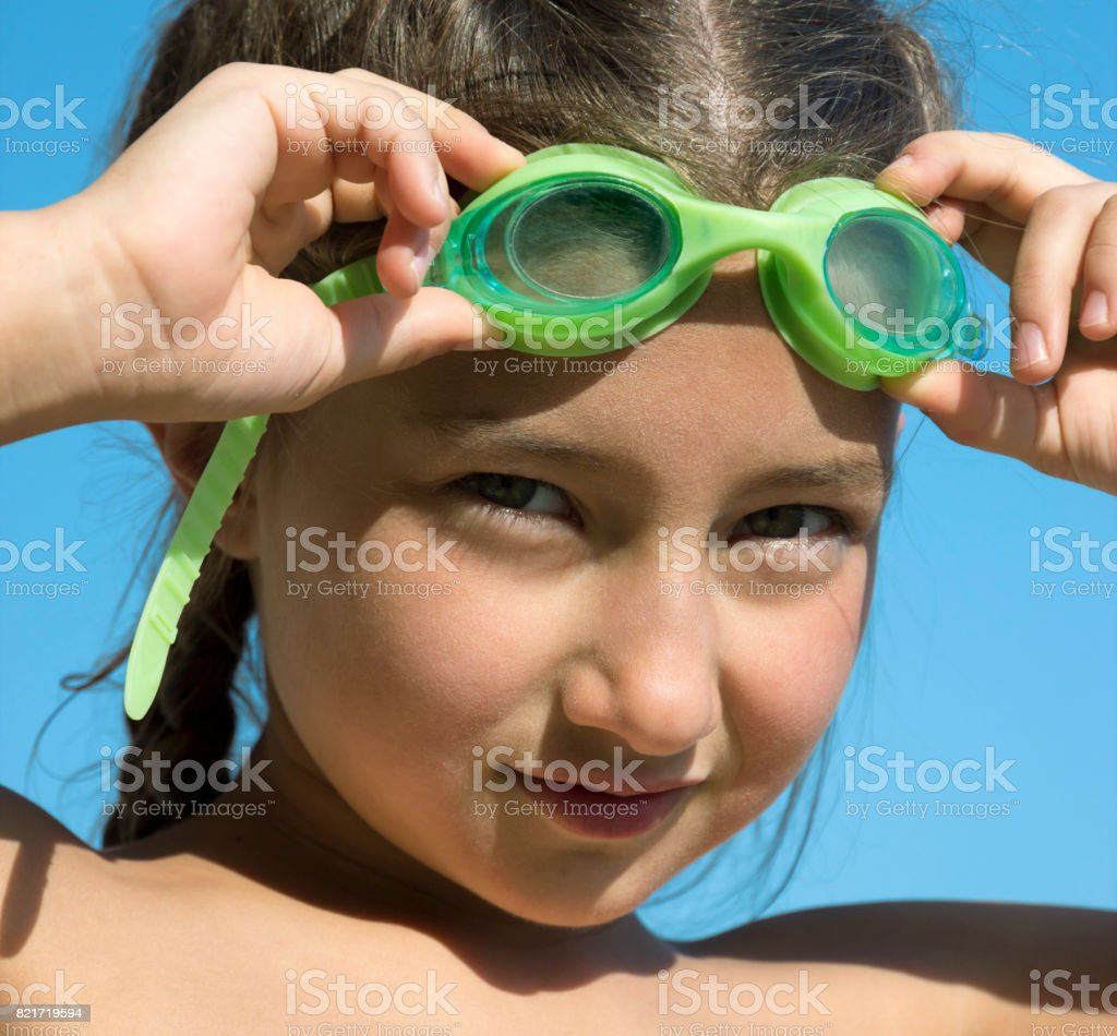 Little girl with underwater glasses Looks attentively at the photographer stock photo