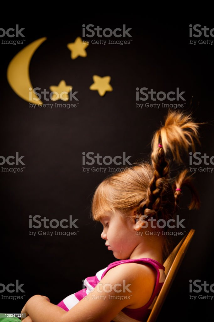 Little Girl with Upward Braids Sleeping Under Moon and Stars royalty-free stock photo