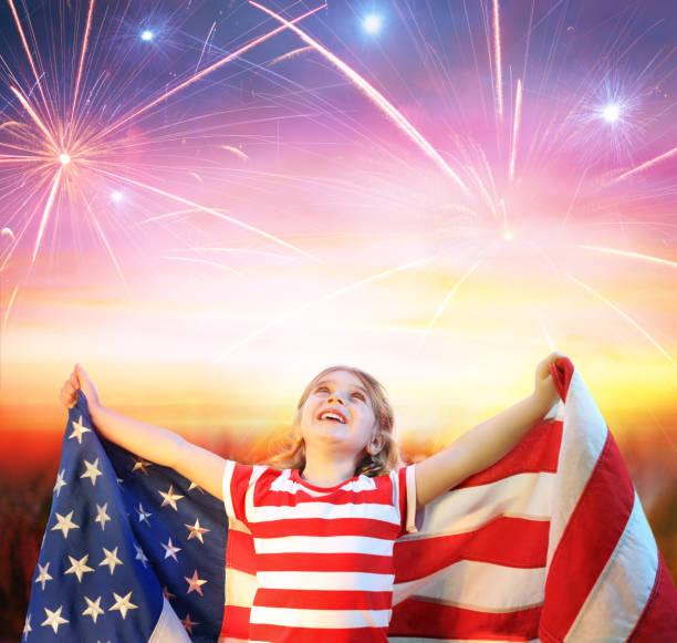 Little Girl With Usa Flag Celebrating Under Fireworks stock photo