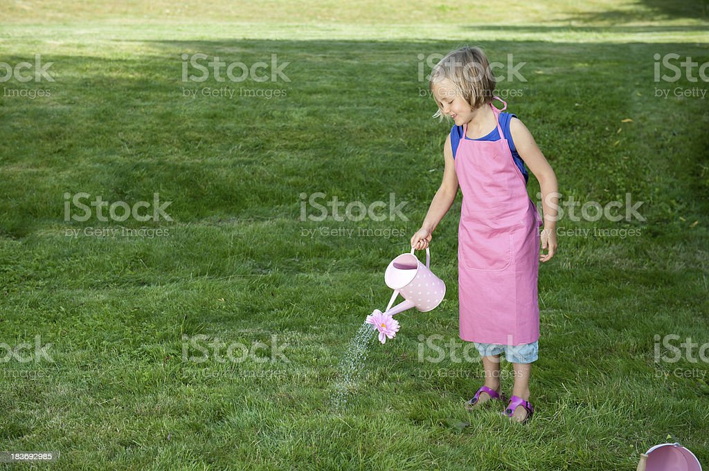 little girl with watering can in the garden stock photo