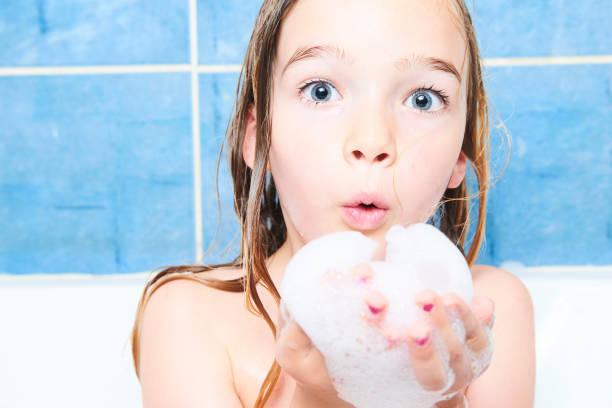 kleines mädchen mit langen nassen haaren nimmt einen schaumbad - mädchen dusche stock-fotos und bilder