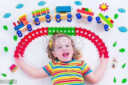 istock Little girl with wooden train 476541162