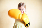 Little girl with yellow boxing gloves over yellow wall background. Girl power concept. Funny little kid portrait. Happy lost tooth little girl portrait