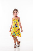 little girl with yellow dress over white background