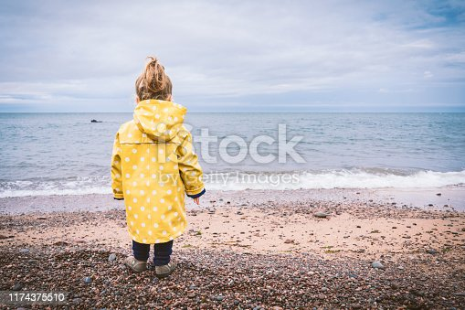 istock little girl with yellow raincoat on the beach in autumn rainy day 1174375510