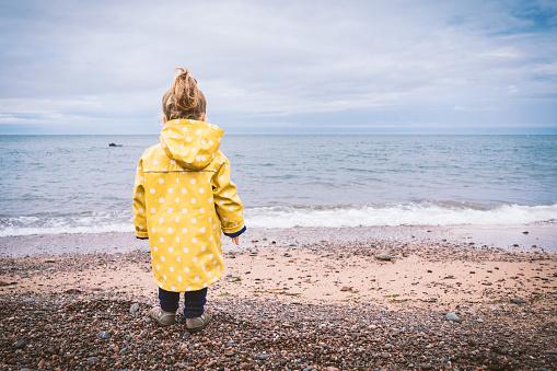 istock little girl with yellow raincoat on the beach in autumn rainy day 1174375510