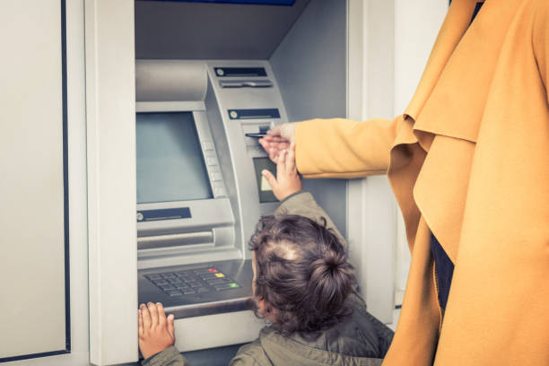 little girl withdrawing money form atm with help of mother. - банки и банкоматы стоковые фото и изображения