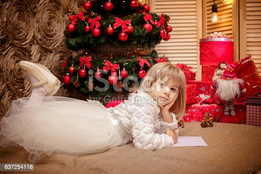 1062609644istockphoto little girl writes a letter to Santa Claus 637254116